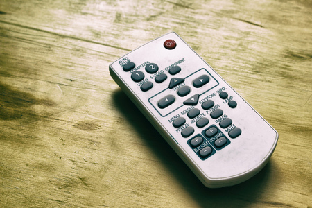 Photograph of a projector remote control on a wood table