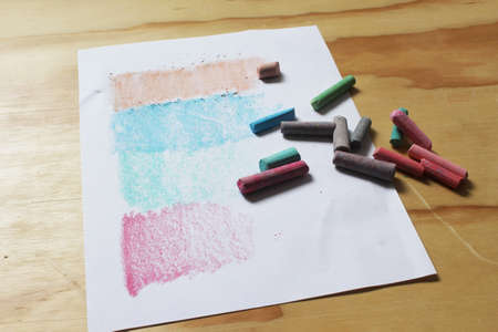 chalks: Photograph of a sheet of paper and color chalks in a retro style on a wood table Stock Photo