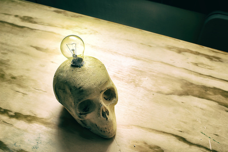dientes sucios: Fotograf�a de un cr�neo humano con una bombilla en una mesa de madera Foto de archivo