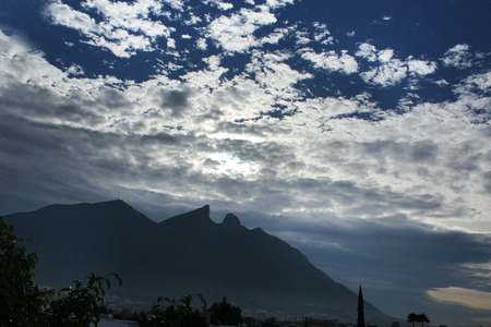 Photograph of a mountain and a cloudy sky. The Cerro de la Silla mountain in the city of Monterrey Mexico