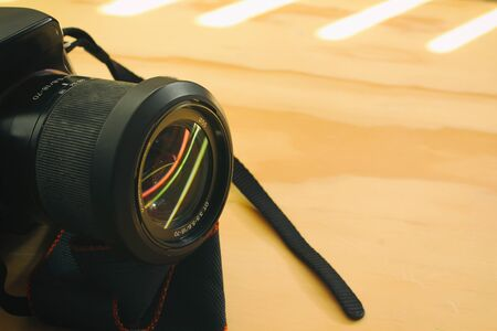 reflex camera: Photograph of a black reflex camera on a wood table Stock Photo