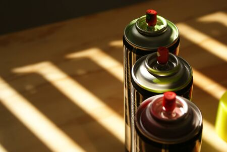 color photographs: Photograph of some spray paint cans on a wood table