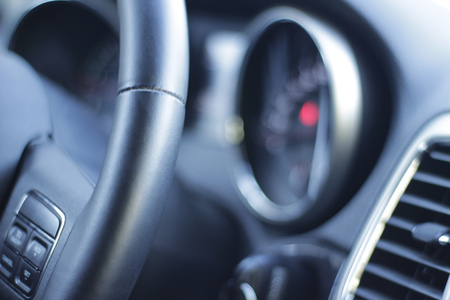 Photograph of a Car steering wheel and instrument cluster