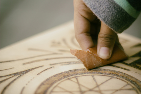 Photograph of a human hand sanding wood