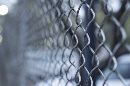 Photograph of a cyclone wire fencing and a blurred background 版權商用圖片
