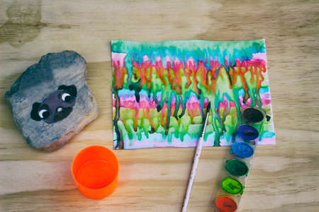 photograph: Photograph of watercolor paint, a brush and a stone with a painted pug dog on it on a wood table