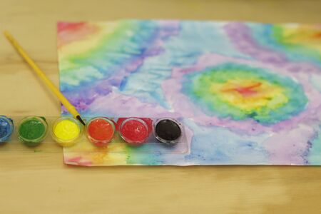 color photographs: Photograph of watercolor paint and a brush on a wood table