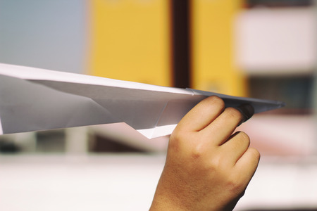 Photograph of a human hand with a paper plane