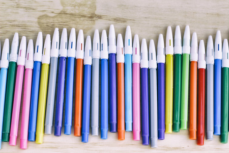 Photograph of some plastic colorful markers on a wood table