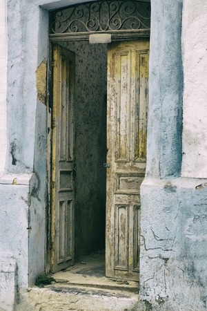 Photograph of an old wood open door and old building Foto de archivo