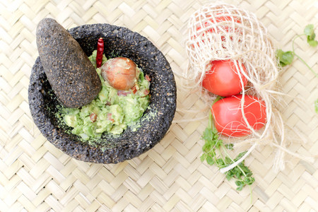 Photograph of smashed advocado, guacamole in a traditional stone molcajete