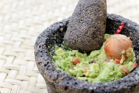smashed: Photograph of smashed advocado, guacamole in a traditional stone molcajete