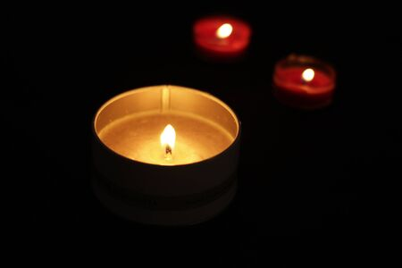 Photograph of three lighted wax candles on a dark black background