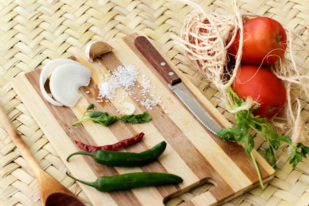 Photograph of a wood cutting board with vegetables