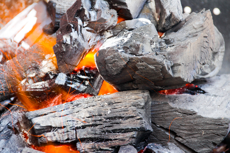 Photograph of some wood charcoal pieces and fire flames Stock Photo