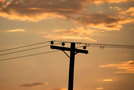 Photograph of an electricity pole and a cloudy sky at sunset