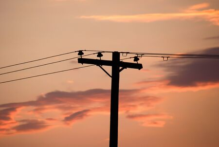 stratus: Photograph of an electricity pole and a cloudy sky at sunset