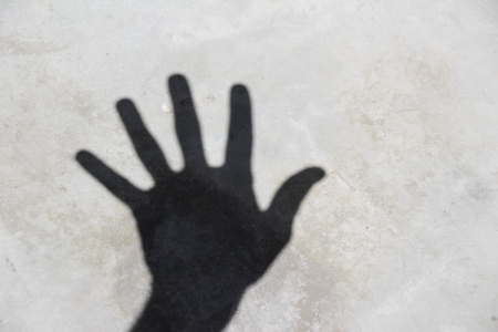 Photograph of an open hand shadow or silhouette on floor