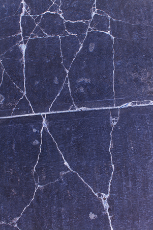 Photograph of a dark cracked concrete texture or background