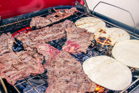 Photograph of some juicy steaks and tortillas on hot grill
