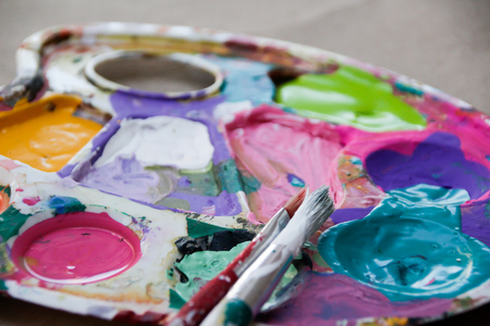 Photograph of an art palette with paint and brushes Stock Photo