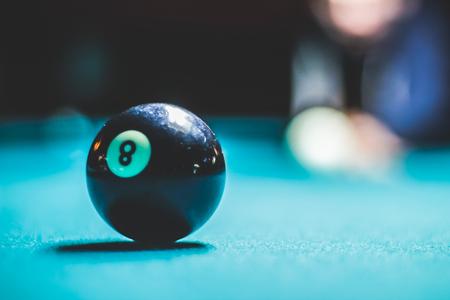 pool bola: Fotografía de una bola ocho de la piscina y la silueta humana borrosa