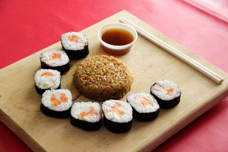 Phtograph of some Sushi roll slices and fried rice on a wood table 版權商用圖片
