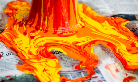 Photograph of some paint pouring out and spilling on a paper