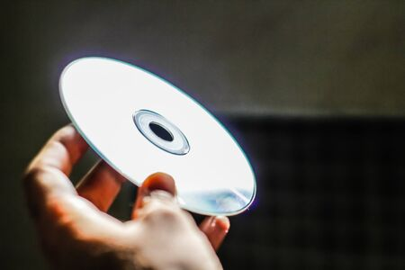 Photograph of a human hand holding a compact disk Stock Photo