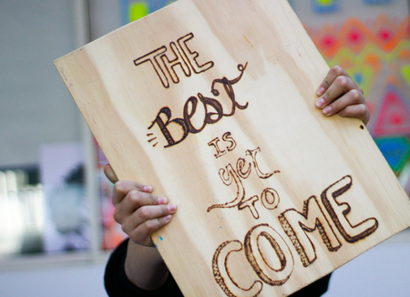 Photograph of a person holding a piece of wood with the phrase: The best is yet to come
