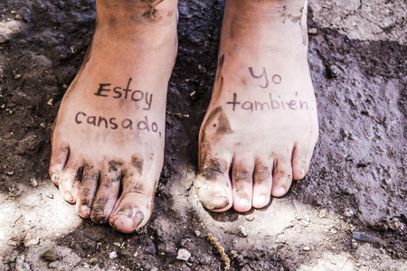 Photograph of a pair of human feet and the phrase in spanish: Estoy cansado, yo tambien, which means: Im tired, me too