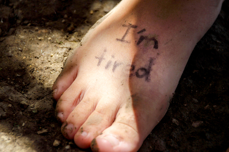 Photograph of a human feet and the phrase: Im tired