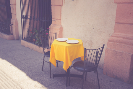 Photograph of a table, two chairs and a yellow tablecloth
