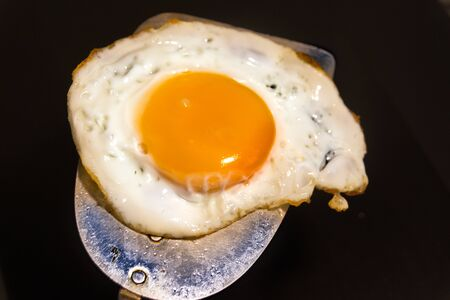 Photograph of a fried egg and metal spatula Imagens - 84391744