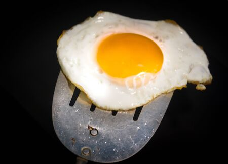 Photograph of a fried egg and metal spatula Imagens - 84391745