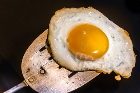 Photograph of a fried egg and metal spatula Imagens - 84391815