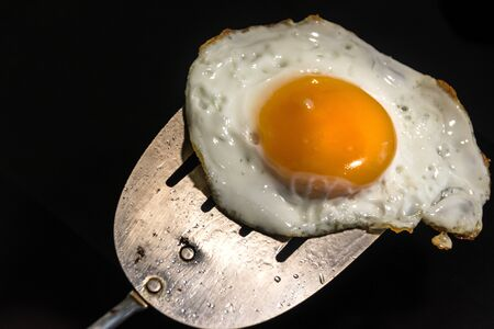 Photograph of a fried egg and metal spatula Imagens - 84391791