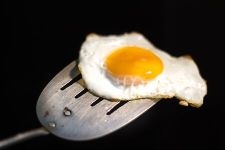 Photograph of a fried egg and metal spatula Imagens - 84391727