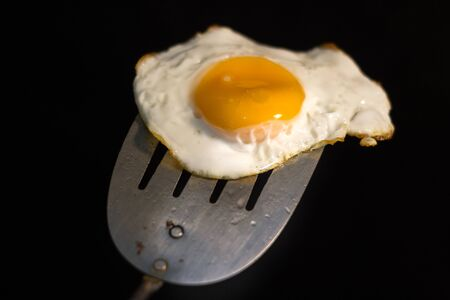 Photograph of a fried egg and metal spatula Imagens - 84391792