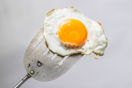 Photograph of a fried egg and metal spatula Imagens - 84391771