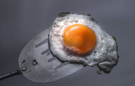 Photograph of a fried egg and metal spatula Imagens - 84391730