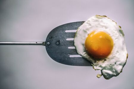 Photograph of a fried egg and metal spatula Imagens - 84391817