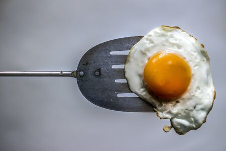 Photograph of a fried egg and metal spatula