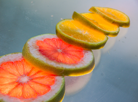 Photograph of a grapefruit and orange slices on lighted glass