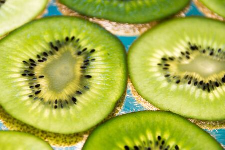 Photograph of some green kiwi fruit slices on lighted glass