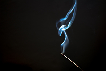 Photograph of an Incense bar and smoke on dark background