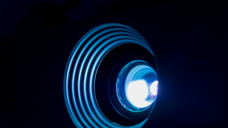 Photograph of a lighted projector lens