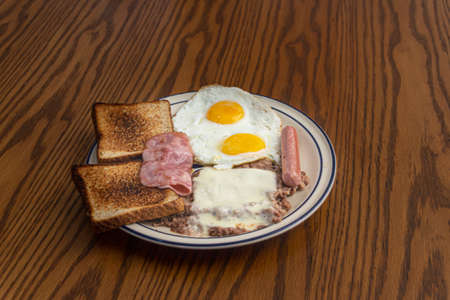 Photograph of a plate with fried eggs, ham, sausage and beans