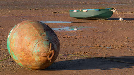Low tide, ships and a buoy Stock Photo