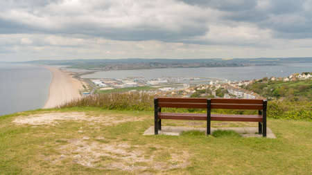A bench on the South West Coast Path  with view towards Fortuneswell and Chesil Beach, Isle of Portland, Jurassic Coast, Dorset, UK - with clouds over Weymouth in the background Stock Photo